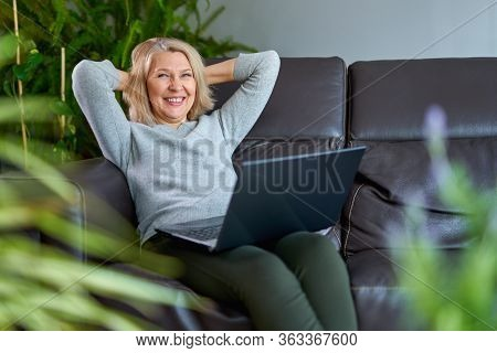 Happy Woman On A Sofa At Home Concentrating As She Works On A Laptop