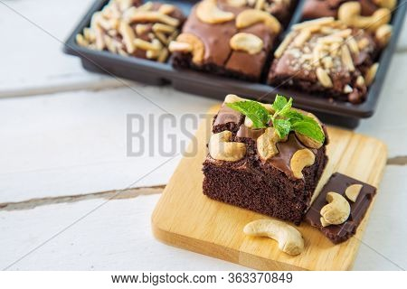 Chocolate Brownies With Cashew Nut And Papermint On Wooden Plate On White Wooden Floor With Brownies