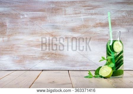 Detox Infused Water With Cucumber, Lime And Mint In Sports Bottle, With Cut Pieces Of Cucumber And L