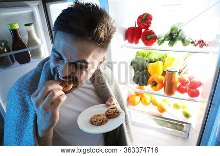 Young Man Eating Cookies Near Open Refrigerator At Night