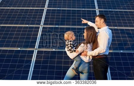 Back View Of A Beautiful Young Family, Standing Together Holding A Baby Near Photovoltaic Solar Pane