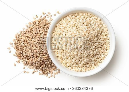 Peeled Sesame Seeds In A White Ceramic Bowl Next To A Pile Of Unpeeled Sesame Seeds Isolated On Whit