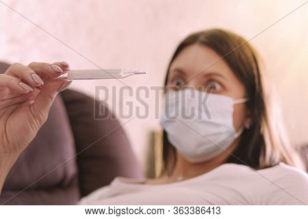 Girl In A Mask From A Virus With Thermometer In Hands. Coronovirus Epidemic. Temperature, Thermomete