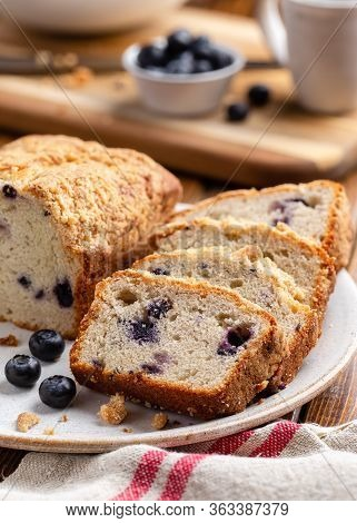 Closeup Of Sliced Blueberry Streusel Loaf Bread And Fresh Berries On A Plate