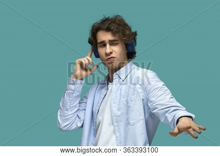 Portrait Of A Young Beautiful Man Wearing White T-shirt And Blue Shirt In Blue Headphones. Poses Lik