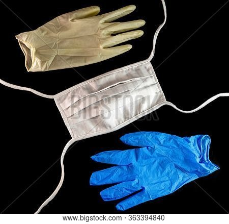 Face Mask And Protective Chirurgical Gloves On Black Baskground