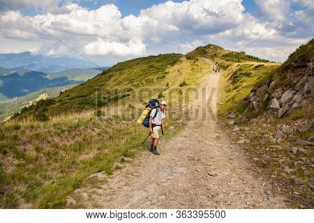 Hiker With Backpack Going Uphill. Hike In Carpathian Mountains. Hiker Going Up To The Mountain Peak