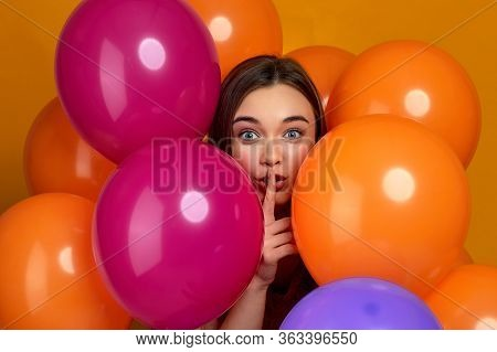 Smiling Caucasian Girl Posing With Bright Color Air Balloons Showing Silence Gesture. Beautiful Happ