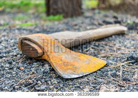 An Old And Rusty Ax Thrown Somewhere In The Forest And Forgotten Lies On The Ground