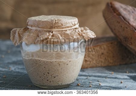 Fresh Rye Sourdough In Glass Jar And Loaf Of Whole Grain Bread, Yeast-free Leaven Starter For Health