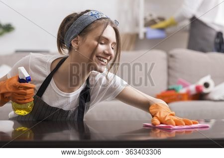 Happy Young Housewife Doing Spring-cleaning At Home, Wiping Dust From Table, Washing Surface With Ra