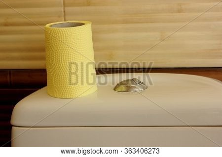 Roll Of Toilet Paper Is On The Toilet. Yellow Toilet Paper. The Toilet Is Ceramic, White. The Wall I
