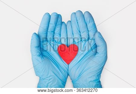 Hands In Medical Gloves Holding A Red Heart Shape Model On White Background. Cardiology. Organ Donat