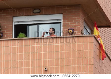 A man drinks wine from his balcony  after Spain imposed a lockdown to slow down the spread of the coronavirus disease in Valencia, Spain on April 10, 2020.