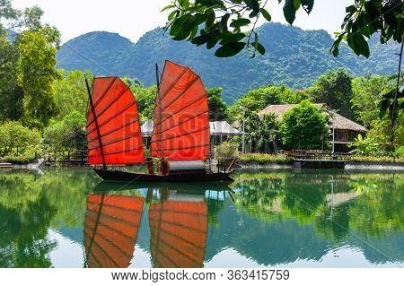 Junk. Beautiful Traditional Vietnamese Boat With Red Sails On A Picturesque Lake In The Jungle. Red