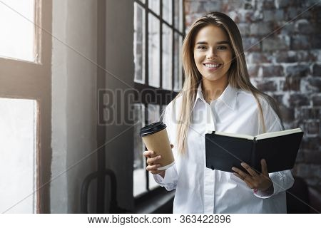 Beautiful Business Woman In White Shirt Is Standing By The Window, Holding Coffee And Black Notebook