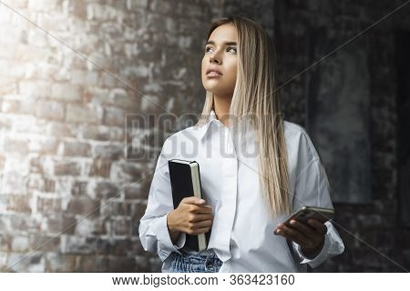 Beautiful Woman Standing In Brick Wall Background. Freelance Jobs For Young Specialists. Student Wit