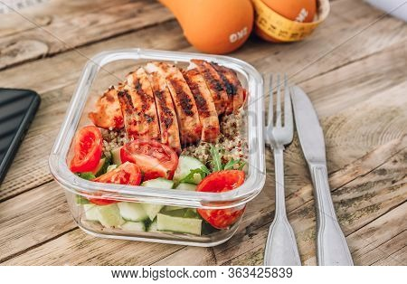 Healthy Meal Container With Dumbbells, Tape Measure And Smartphone On Wooden Background. Online Diet