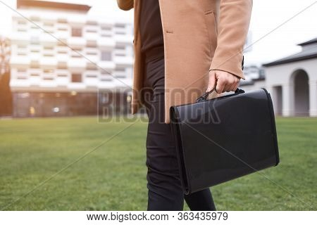 Business Man In A Brown Coat And A Bag With Documents In His Hands Goes To Wor
