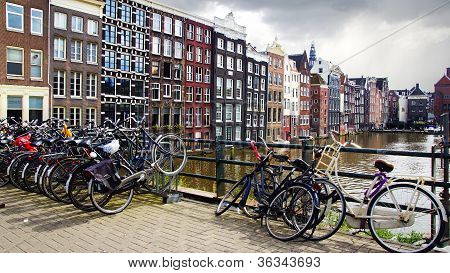 Many bicycles parked in front of the traditional houses.