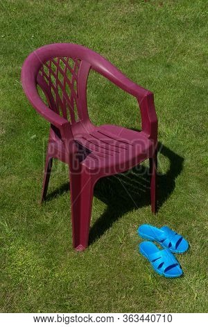 Plastic Flip-flops And A Plastic Chair On The Grass. No One. Vacation In Nature. The Quarantine Cont