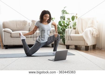 Training On Isolation. Sporty Young Woman Practicing Yoga In Front Of Laptop, Watching Online Tutori