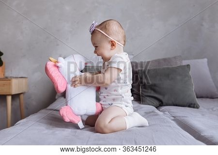 Lovely Smiling Little Girl With A Hoop Is Playing With Toy Unicorn On Bed At Home. Concept Of Childh