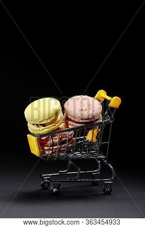 Macaroons In Metal Shopping Basket. Studio Photo. Macaroons On Dark Background, Colorful French Cook