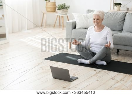 Yoga Online. Relaxed Senior Woman Meditating In Front Of Laptop At Home, Sitting In Lotus Position A