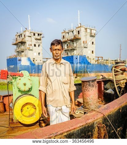 Chittagong, Bangladesh, December 22, 2017: Portrait of a skipper of a boat on the Karnaphuli River with shipyard in the backdrop