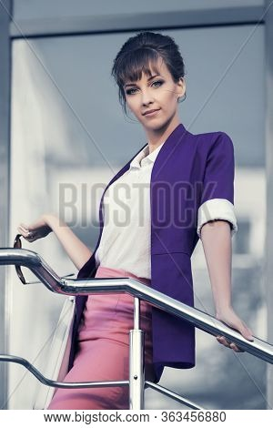 Happy young fashion business woman at office building Stylish female model in purple blazer white shirt and pink pencil skirt