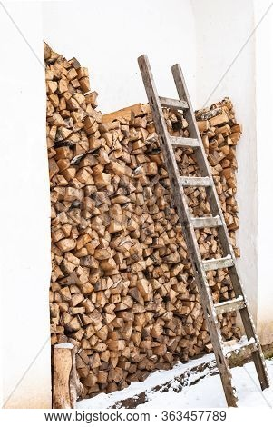Dry Harvested Firewood In A Woodpile For A Stove Or Fireplace. A Wooden Staircase Attached To A Wood