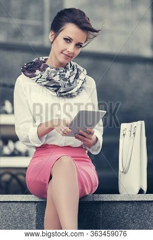 Young fashion business woman using tablet computer at office building Stylish female model in white shirt and pink pencil skirt