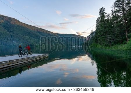 Paul Lake Provincial Park, Canada - June 29, 2020: People On Bicycles On Wooden Dock Facing A Calm L