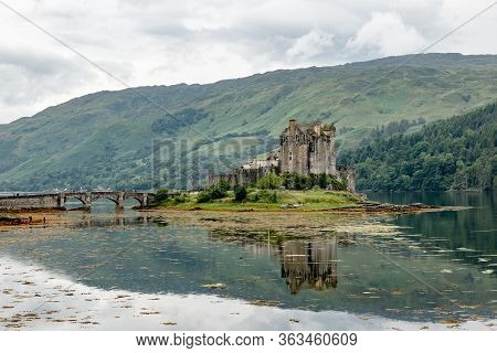 Reflection Of Eilean Donan Castle, Scotland, Uk In Waters Of Loch Duich In Typical Scottish Cloudy W