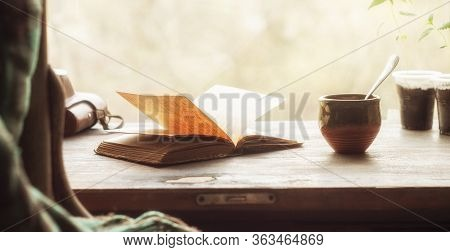 Cup Of Coffee And An Open Old Book On A Wooden Windowsill