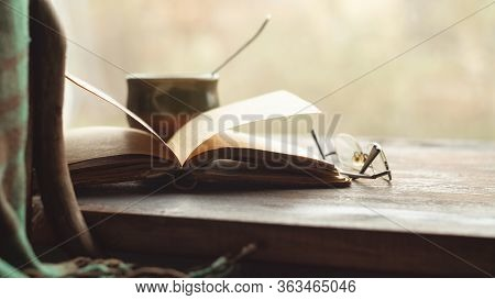 Cup Of Coffee, Old Book And Glasses On The Windowsill, Near A Chair With A Plaid