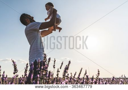 Spanish Father Lifting Her Child Under Sunset. Silhouette Of Mother And Son At Sunset. Family Having