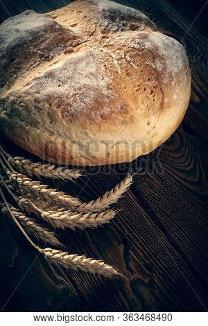 Homebaked Bread. Peasant Round Bread And Wheat Spikelets On A Wooden Background. Homemade Baking. To