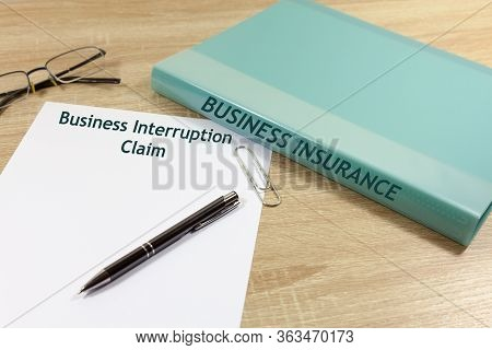 Business Interruption Claim Concept - With Folder That Reads Business Insurance