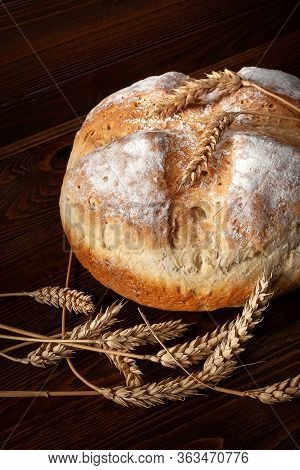Homebaked Bread. Close-up Of A Loaf Of Warm Fresh Peasant Bread And Wheat Spikelets On A Wooden Back