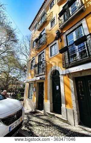 Lisbon, Portugal- March 7, 2020: Old Colorful And Beautiful Facades With Vintage Streetlight In Lisb
