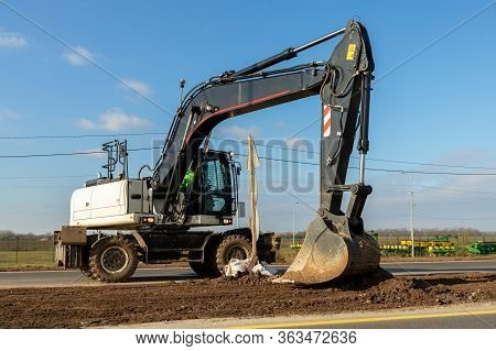 Big White Modern Wheeled Excavator Digging And Mowing Earth At Infrastructure Highway Road Construct