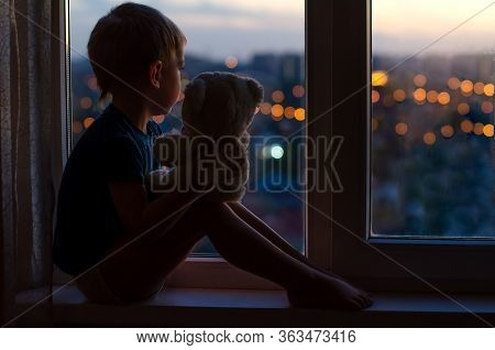 Child - A Little Boy Sitting On The Window With A Teddy Bear At Home. Background Blurry Lights Of Th