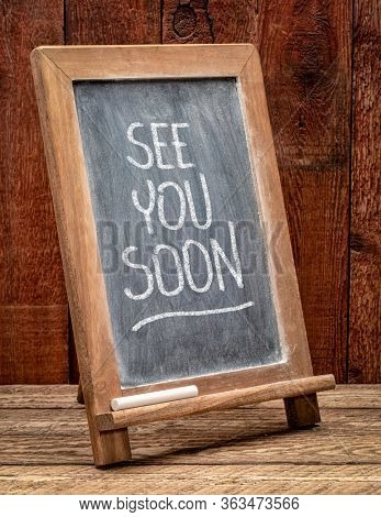 see you soon blackboard sign with white chalk smudges against rustic barn wood, business invitation concept