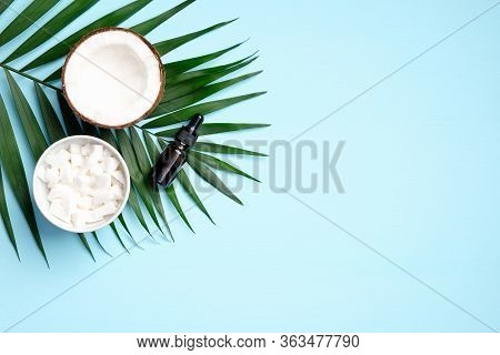 Flat Lay Composition With Coconut Oil On Blue Background. Top View Half Coconut, Sliced Coconut In B