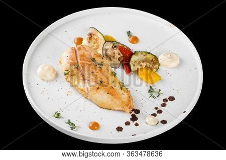 Grilled Chicken Breast Served With Baked Vegetables. Isolated On A Black Background.