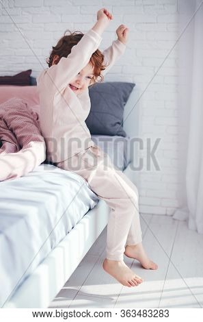 Cheerful Redhead Baby Boy Getting Up In The Morning At Sunny Bedroom