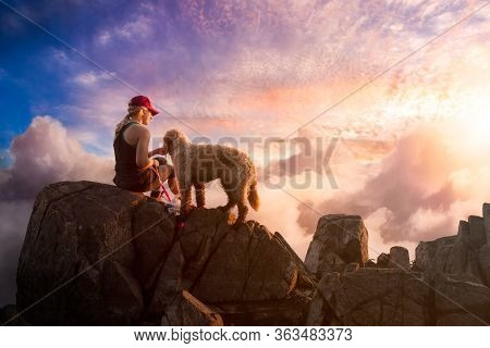 Adventurous Girl Is Hiking With A Dog On Top Of Rocky Mountain Over The Cloudscape During A Sunny Su