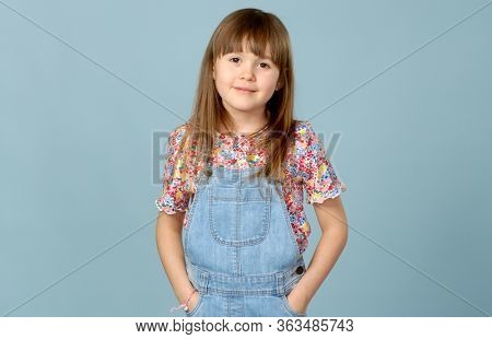 Cute little girl standing in dungarees jeans with hands in pockets. Looking at camera with smile. Isolated portrait on blue studio background.